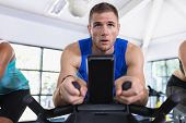 Close-up of Caucasian fit men exercising on exercise bike in fitness center. Bright modern gym with  poster