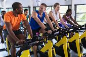 Front view of diverse fit people exercising on exercise bike in fitness center. Bright modern gym wi poster