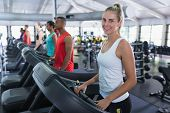 Portrait of Caucasian fit woman exercising on treadmill in fitness center. Bright modern gym with fi poster