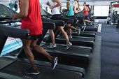 Low section of diverse fit people exercising on treadmill in fitness center. Bright modern gym with  poster