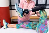 Mid section of Caucasian female trainer assisting disabled Caucasian active senior woman to stretchi poster