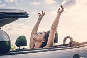 Happy Girl Relaxing Enjoying Sunshine Sitting In Convertible Car On Summer Road Trip Vacation Drivin poster