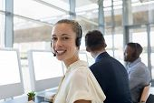 Portrait of a young Caucasian woman working in a call centre sitting at a computer wearing a headset poster