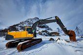 Old excavator with excavator bucket in winter. Road construction in snow. Lofoten islands, Norway poster