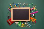 Blank blackboard and stationery accessories: pencils, pens, other office supplies on green backgroun poster