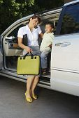 Full length of a happy business woman assists her son to get down from car