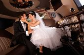 stock photo of fondling  - Happy couple embracing in limousine on wedding - JPG
