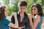 stock photo of threesome  - Young man and two women looking at him - JPG