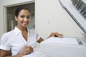 Portrait of a happy Indian business woman using fax machine in office
