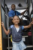 stock photo of bus driver  - Portrait of a cute little girl getting down from the bus while driver looking at her - JPG