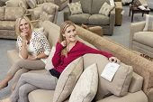 Happy mother and daughter sitting on sofa in furniture store