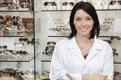 Portrait of a beautiful optometrist with arms crossed in store