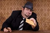 stock photo of payday  - Smoking gangster holding brown envelope, close up.