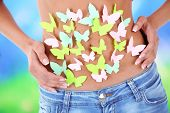 stock photo of belly-band  - Butterfly on stomach on light background - JPG