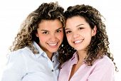 Happy twin sisters smiling - isolated over a white background