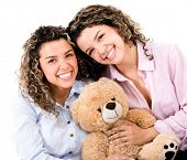 Loving female twins holding a teddy bear - isolated over white