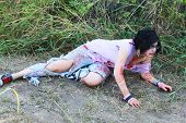 image of gruesome  - Bloody woman with a ripped shirt wonders in a field - JPG