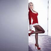 foto of stiletto  - Sexy blonde woman posing in red dress christmas style - JPG