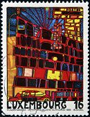 A stamp printed in Luxembourg shows the House with the Arcades and the Yellow Tower by Hundertwasser