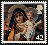 A stamp printed in the United Kingdom shows The Virgin mary with Infant Christ