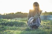 Fashionable young girl crouching in sheer dress and jacket staring at camera in a meadow