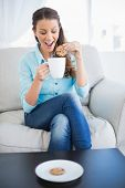 Happy woman dunking biscuit into hot chocolate sitting on cosy sofa