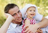 stock photo of father time  - Happy young father spending time outdoor on a summer day with his beautiful daughter - JPG