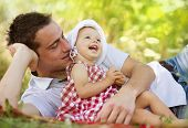 foto of father time  - Happy young father spending time outdoor on a summer day with his beautiful daughter - JPG
