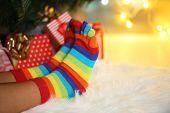 Legs in socks near Christmas tree on carpet