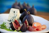 Plate of Italian delicacies, starter - figs, prosciutto, gorgonzola and rucola