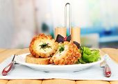 Chicken Kiev on croutons with lettuce salad, on wooden table, on bright background