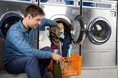 Young man putting clothes in washing machine at laundromat