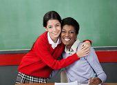 Portrait of happy schoolgirl hugging professor at desk in classroom