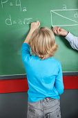 Rear view of little boy writing formula on greenboard in classroom