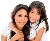 Beautiful mother and daughter smiling - isolated over a white background