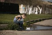 little boy plays with paper boats in puddle