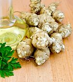 stock photo of jerusalem artichokes  - Jerusalem artichoke tubers with parsley and carafe with vegetable oil on the background of wooden boards - JPG