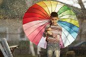 happy boy with a rainbow umbrella in park