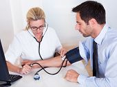 image of sphygmomanometer  - Attractive young female doctor or nurse taking a male patients blood pressure using a sphygmomanometer - JPG