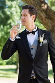 Young thoughtful bridegroom drinking champagne in garden