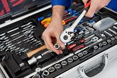 Portrait Of Automechanic Taking A Wrench Out Of Toolbox