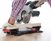Worker Cutting Timber Using Circular Saw