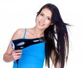 Beautiful smiling young woman drying her hair with hairdryer - isolated on white