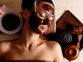 Spa therapy for young woman having cosmetic mask at beauty salon