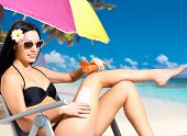 Beautiful happy woman in black bikini applying sun block cream on the tanned body.  Girl  holding or