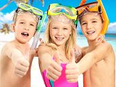 Portrait of the happy children with thumbs-up gesture at beach.  Schoolchild kids standing together