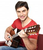 Smiling guitarist plays on the acoustic guitat  isolated on white background. Handsome young man sits with guitar on divan
