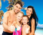 stock photo of suntanning  - Portrait of  happy smiling family with thumbs up sign  at tropical beach - JPG