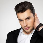 picture of enticing  - Closeup face of a fashion young businessman in black suit casual  poses at studio - JPG