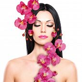 Young woman with beautiful face and fresh flowers. Skin care concept.
